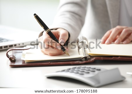 Close-up of businesswoman holding pen in hands and writing a note.