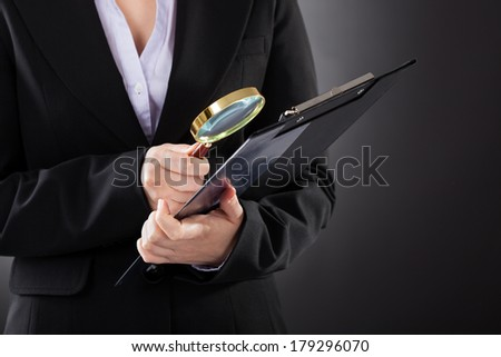 Close-up Of Businesswoman Looking Through Magnifying Glass To Clipboard - stock photo