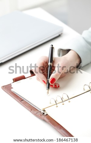 Close-up of businesswoman's hand while writing note in diary. Small business.