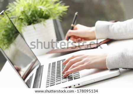 Close-up of businesswoman's hands doing paperwork. - stock photo