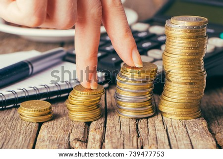 Close-up Of Businesswoman's Hands with money coins in office on wooden desk