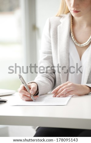 Close-up of businesswoman sitting at desk and fill the form.