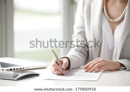 Close-up of businesswoman sitting at desk and fill the form.  - stock photo