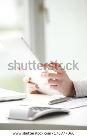 Close-up of businesswoman sitting at desk and typing on tablet in office.