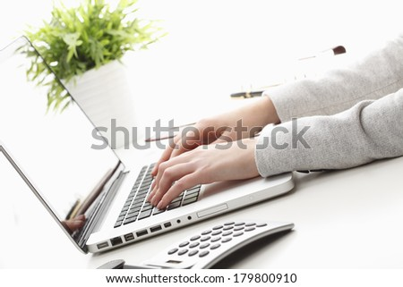 Close-up of businesswoman sitting while working on laptop and calculating. - stock photo