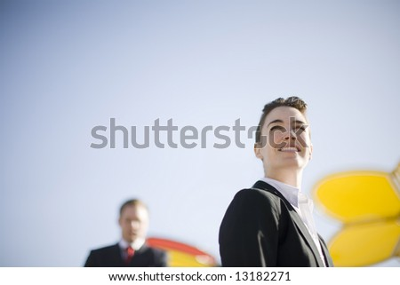 close up of businesswoman standing looking away with businessman standing in background - stock photo