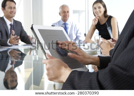Close Up Of Businesswoman Using Tablet Computer During Board Meeting Around Glass Table - stock photo