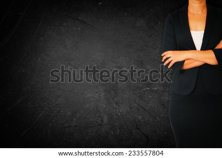 Close up of businesswoman with arms crossed against dark textured background - stock photo