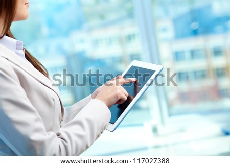 Close-up of businesswoman working with touchpad in office - stock photo