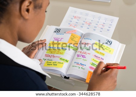Close-up Of Businesswoman Writing Schedule In Calendar Diary - stock photo