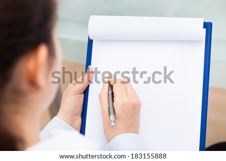 Close-up Of Businesswoman Writing With Pen  On Clipboard - stock photo