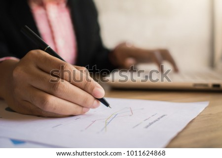 Close up of businesswomen checking paper report on desk in office,selective and soft focus