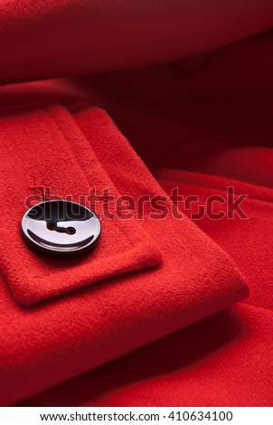 Close-up of button on red coat. - stock photo