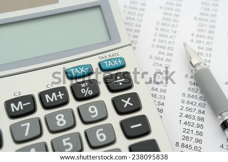close up of calculator and document with pen, focus on blue tax buttons - stock photo