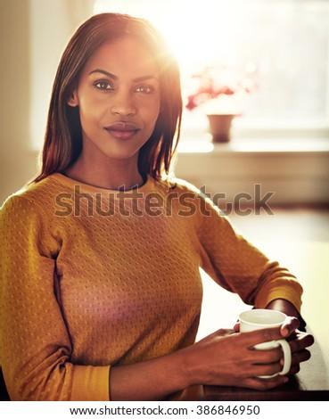 Close up of calm beautiful black single female in yellow sweater holding white mug next to bright sunlight in window - stock photo