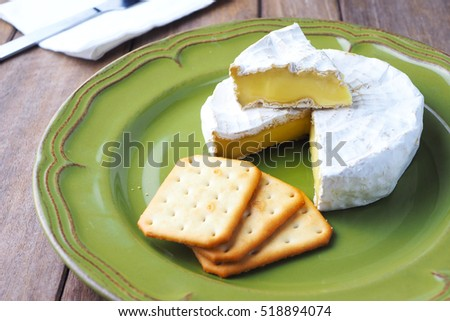 Close up of camembert cheese and crackers on a wooden table.
