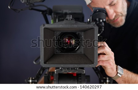 close-up of camera operator working with a cinema camera