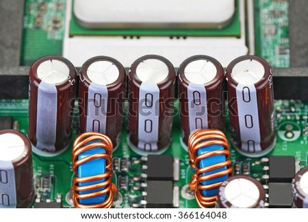 Close up of capacitor on printed computer circuit board - stock photo