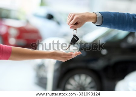 Close up of car dealer giving keys to woman - stock photo