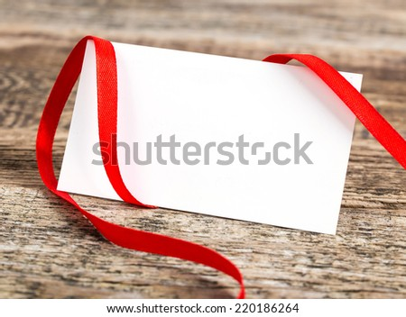 close up of card note with ribbon on wooden desk - stock photo
