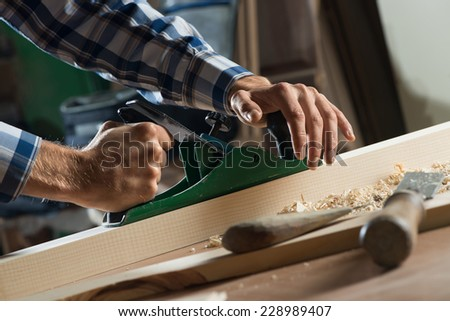 Close up of carpenter's hands working with the jointer