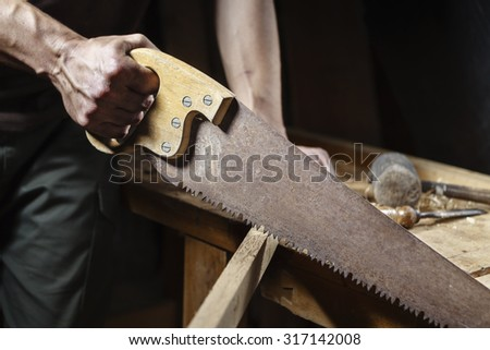 close up of Carpenter sawing a board with a hand wood saw  - stock photo