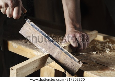 close up of Carpenter sawing a board with a hand wood saw
