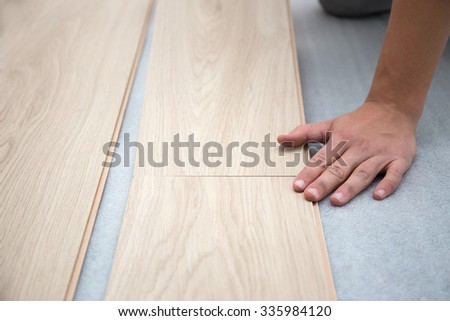 close up of carpenter worker installing laminate flooring in the room - stock photo