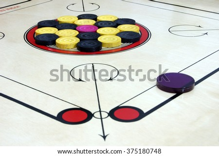 Close up of Carrom board or Karrom with striker, carrom men, and queen