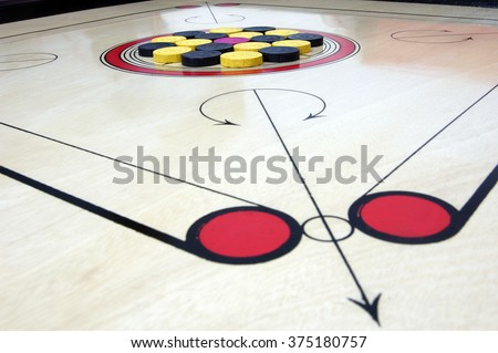 Close up of Carrom board with striker and coins