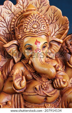Close-up of carved idol of Hindu god Ganesha - Lorf of good omen against a dark background - stock photo