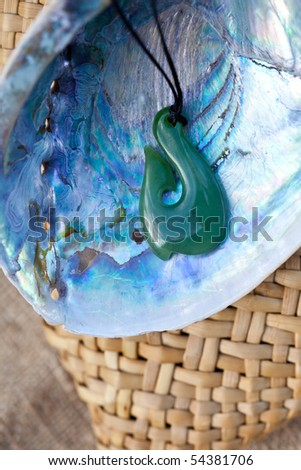 close up of carved maori nephrite jade / greenstone pendant on paua shell with kite bag in background