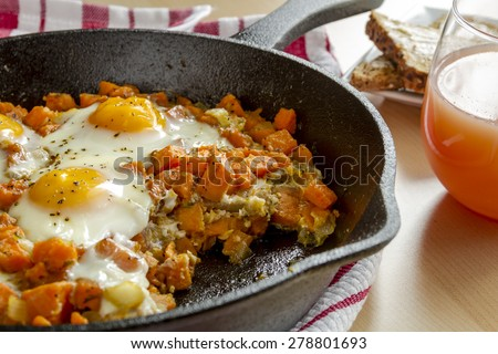 Close up of cast iron skillet filled with fried eggs and sweet potato hash with grapefruit juice and whole grain toast