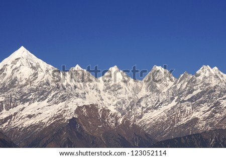 close up of chain of five snow clad mountain peaks - stock photo