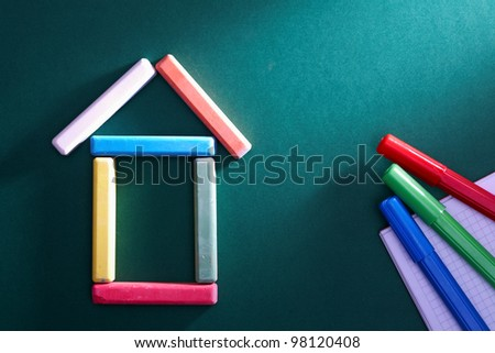 Close-up of chalk house and highlighters on blackboard - stock photo