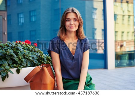Close-up of charming smiling elegant woman sitting on bench with flower pot on the background of mirror glass modern building - stock photo