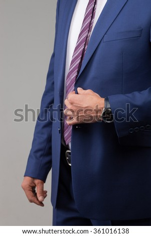 Close up of cheerful businessman is wearing his suit for an appointment. He is standing. Isolated - stock photo