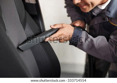 Close up of cheerful car repair shop worker is cleaning the interior of the car. He is holding a vacuum cleaner and touching it to the seat. The man is smiling - stock photo
