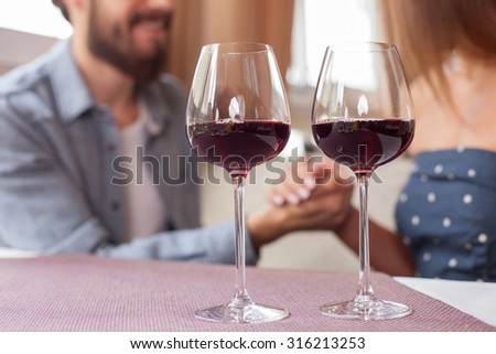 Close up of cheerful man and woman sitting at the table in cafe. They are holding hands with love and smiling. Focus on two glasses of red wine