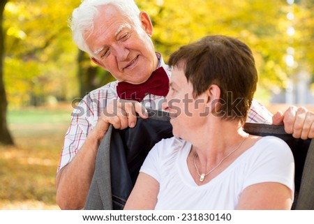 Close-up of cheerful man covering his wife by coat