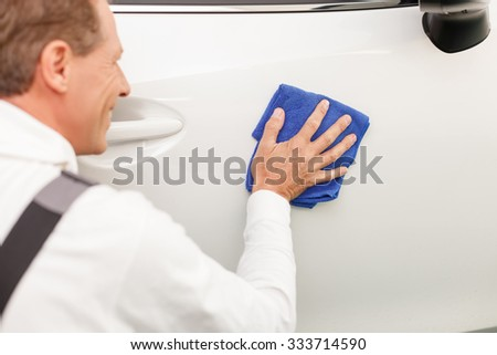 Close up of cheerful mid aged mechanic washing the car with cloth. He is kneeling and smiling - stock photo