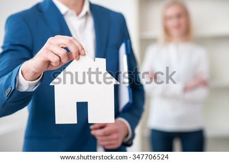 Close up of cheerful realtor selling an apartment. He is holding a placard in the shape of house. The woman is standing on background - stock photo