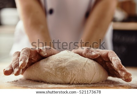 Close-up of chef hands kneading raw dough of wooden board. Baking concept.
