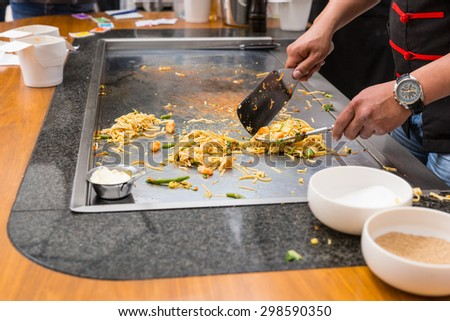 Close Up of Chef Preparing Single Serving Portions of Stir Fried Noodles on Flat Top Grill - stock photo