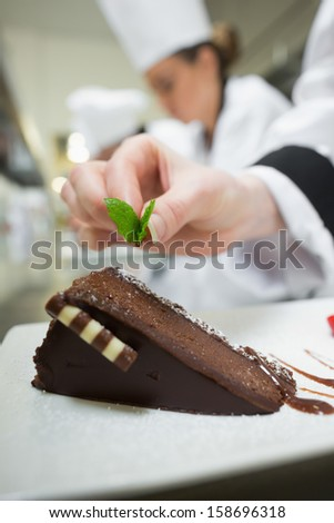 Close up of chef putting mint leaf on chocolate dessert in busy kitchen - stock photo