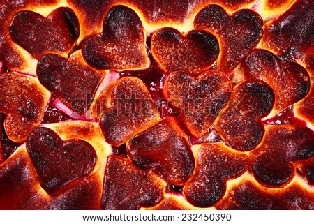 Close up of cherry pie with hearts as background - stock photo