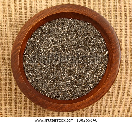 Close Up Of Chia Seeds In Wooden Bowl On Burlap Bag - stock photo