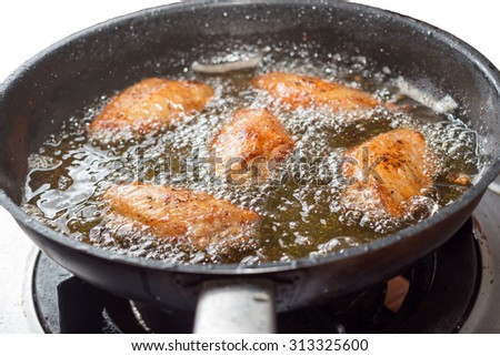 Close up of chicken frying in a pan. - stock photo