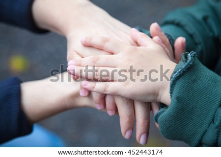 Close up of child and mother gathering hands and supporting each other.