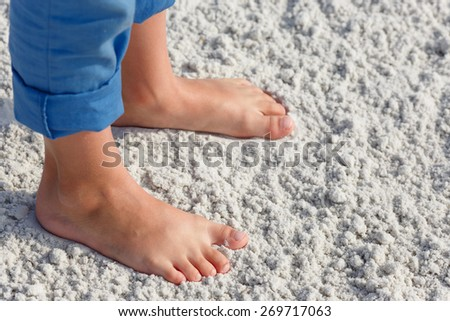 Close up of child feet on a tropical sandy beach, Florida, Siesta Key beach